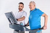 rehabilitation therapist assisting senior man exercising on treadmill isolated on grey