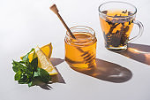 healthy tea with lemon, mint and honey on white tabletop