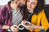 Young man kissing his girlfriend while they holding coffee cups