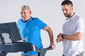 rehabilitation therapist checking time while assisting senior man exercising on treadmill isolated on grey