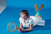 female tennis player lying with tennis racket on blue