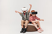 adorable little children playing in virtual reality headsets isolated on grey