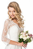 curly young bride with bouquet isolated on white
