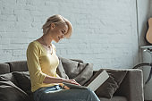 side view of smiling girl sitting with laptop on sofa