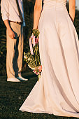 cropped shot of young bride in beautiful dress holding wedding bouquet