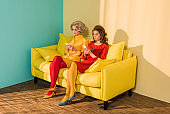 retro styled women using smartphones while resting on yellow sofa, doll house concept