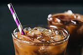 selective focus of glass of cold iced coffee with straw on dark background
