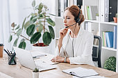 beautiful serious female operator working with headset and laptop in office