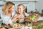 Mother and daughter playing with food