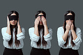 woman in black blindfold closing ears, eyes and mouth