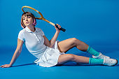sexy Tennis player sitting with tennis racket and looking away on blue
