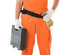 cropped image of auto mechanic in orange uniform holding toolbox isolated on white
