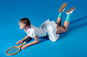 sexy Female tennis player lying with tennis racket on blue