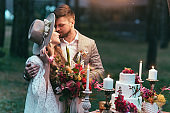 beautiful couple on wedding standing near cake and candles