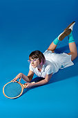 seductive Female tennis player lying on belly with tennis racket on blue