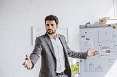 handsome businessman presenting project on flipchart and gesturing in office
