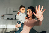 happy attractive woman holding little son and waving by hand at home