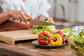 cropped image of woman preparing salad for dinner and cutting cabbage at home, bell peppers on foreground