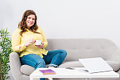 Portrait of young plus size woman with cup of coffee sitting on sofa with laptop at home