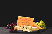 Different types of cheese on board with grapes on black