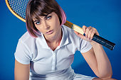 female tennis player with tennis racket looking at camera isolated on blue