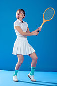 female tennis player standing in pose with tennis racket on blue