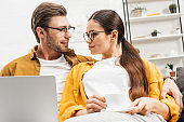 couple with coffee and laptop sitting on couch together at home