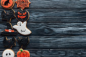 elevated view of arranged halloween homemade cookies placed in rows on black wooden background