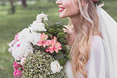 cropped shot of smiling blonde bride holding beautiful bouquet of flowers outdoors