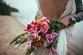 cropped view of bride and groom holding wedding bouquet and embracing on beach