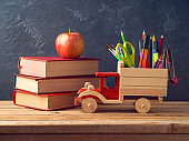 Back to school concept with toy truck and school supplies