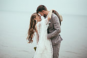 cheerful bride and groom in boho style hugging at lake