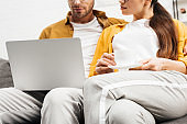 cropped shot of young couple with coffee and laptop sitting on couch together