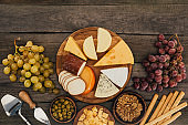 top view of arranged various types of cheese on cutting board, olives, hazelnuts and grapes on wooden surface