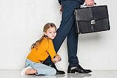 little daughter hugging father in business suit isolated on grey, loneliness concept