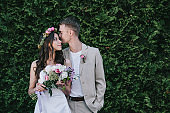 groom kissing and hugging beautiful bride in traditional dress with wreath and wedding bouquet