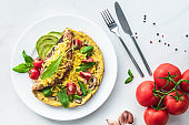 flat lay with omelette with cherry tomatoes, avocado pieces and cutlery on white marble surface