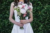 cropped view of bride in traditional white dress holding wedding bouquet