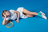 seductive female tennis player lying with tennis racket and looking up on blue