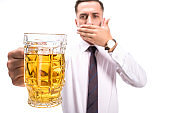 selective focus of businessman covering mouth and holding glass of unhealthy beer isolated on white