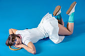 sexy Female tennis player lying with tennis racket and looking at camera on blue