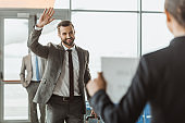 businessman waving to partner who waiting for him with name sign on paper at airport