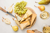 Top view of different types of cheese on wooden board surrounded by knife, fruits, almond, baguette and wine glasses on white