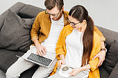 high angle view of young couple with coffee and laptop sitting on couch together