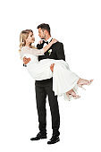 smiling young groom carrying his bride isolated on white