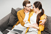 high angle view of couple with coffee and laptop embracing on couch at home