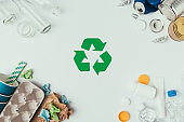 flat lay with arranged different types of garbage and recycle sign isolated on grey