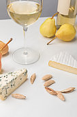 Closeup view of brie and blue cheese with almond, pears, wine glass, bottle and baguette on gray