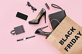 flat lay with high heels, accessories and shopping bag with black friday sign isolated on pink