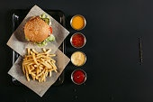 top view of french fries with delicious burger on tray and assorted sauces on black